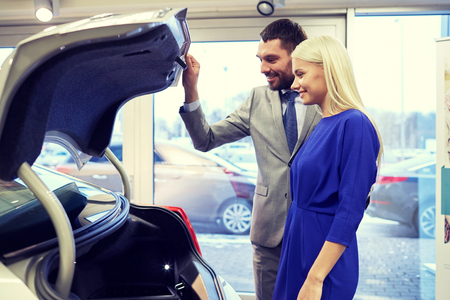 petaca: auto business, car sale, technology and people concept - happy couple with car dealer in auto show or salon