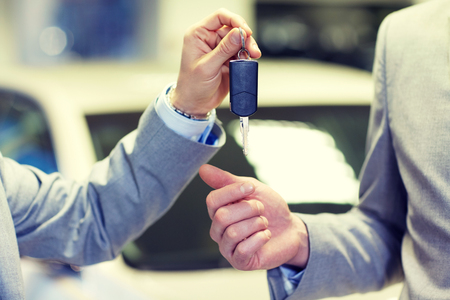 deal in: auto business, car sale, deal and people concept - close up of male hands with car key in auto show or salon Stock Photo