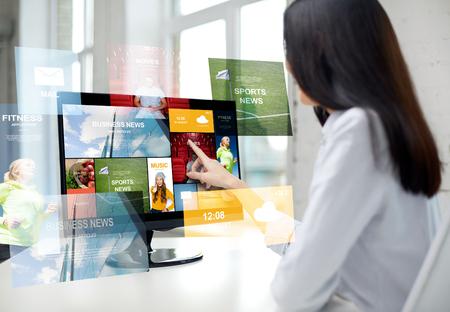 het bedrijfsleven, mensen, technologie en massamedia concept - close-up van vrouw wijzende vinger naar nieuws applicatie op de computer monitor in het kantoor Stockfoto