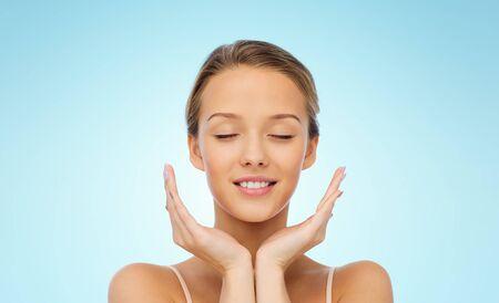 ojos cerrados: belleza, gente, cuidado de la piel y el concepto de salud - joven cara y las manos sobre fondo azul sonriendo