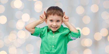 preschool children: childhood, fashion, fun and people concept - happy little boy having fun and making horns over holidays lights background