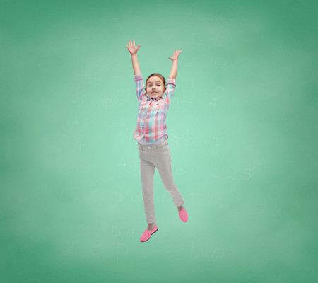 elementary school: school, education, childhood, freedom and people concept - happy little girl jumping in air over green school chalk board background