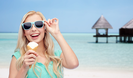 over eating: summer vacation, travel, tourism, junk food and people concept - young woman or teenage girl in sunglasses eating ice cream over beach on touristic resort background