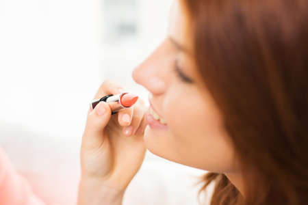 visagiste: beauty, make up, cosmetics and people concept - close up of smiling young woman face and visagist hand applying lipstick