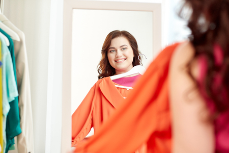 clothing, wardrobe, fashion, style and people concept - happy plus size woman with shirt on hanger at mirror at home Stock Photo