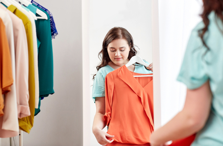 mirror: clothing, wardrobe, fashion, style and people concept - happy plus size woman with shirt on hanger at mirror at home Stock Photo