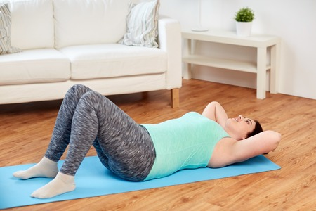 mat: fitness, sport, people and healthy lifestyle concept - plus size young woman exercising on mat at home Stock Photo
