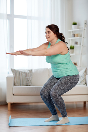 fitness, deporte, ejercicio, el entrenamiento y el concepto de estilo de vida - sonriente mujer de talla grande hacer sentadillas en la estera en el hogar