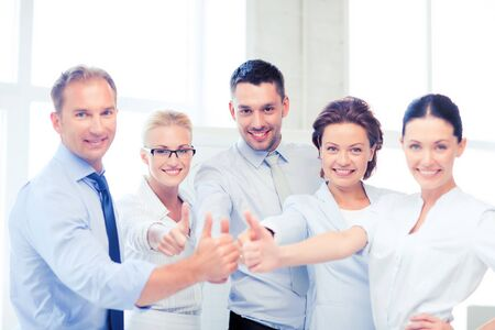 team cooperation: picture of happy business team showing thumbs up in office Stock Photo