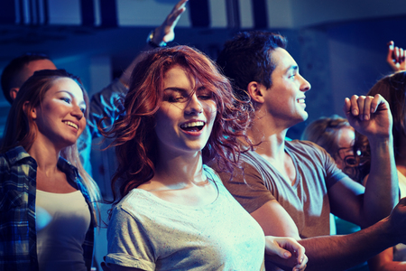 party, holidays, nightlife and people concept - happy friends dancing at night club Stock Photo