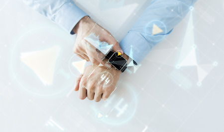 projection: business, future technology and people concept - close up of male hands setting smart watch with virtual screens and charts projection Stock Photo