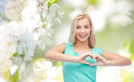 young at heart: gesture and people concept - smiling young woman or teenage girl showing heart shape made of fingers over natural spring background