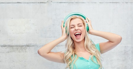 music, technology and people concept - happy young woman or teenage girl with headphones singing song over gray concrete wall background