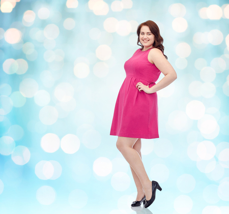 female, gender, portrait and people concept - smiling happy young plus size woman posing in pink dress background over blue holidays lights background