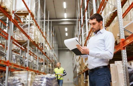 logistics: wholesale, logistic, people and export concept - businessman or supervisor with clipboards at warehouse