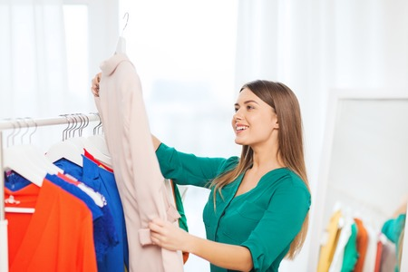 woman closet: clothing, fashion, style and people concept - happy woman choosing clothes at home wardrobe