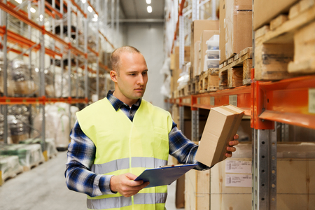merchandise: wholesale, logistic, people and export concept - man with clipboard and box in reflective safety vest at warehouse Stock Photo