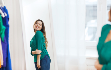 choosing clothes: clothing, fashion, style and people concept - happy woman choosing clothes and posing at mirror at home wardrobe Stock Photo
