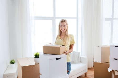 hospedaje: en movimiento, la entrega, el alojamiento y las personas concepto - mujer joven sonriente con una caja de cartón en su casa