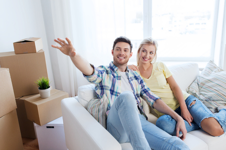 soñando: las personas, la reparación y el concepto de bienes raíces - sonriente pareja con cajas de mudanza al nuevo hogar y el sueño Foto de archivo