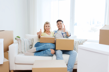 package: moving, people, repair and real estate concept - happy couple with big cardboard boxes showing thumbs up on sofa at new home