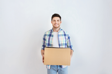 accommodation: moving, delivery, housing, accommodation and people concept - smiling young man with cardboard box at home Stock Photo
