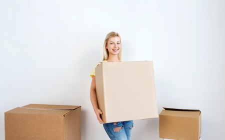 moving, delivery, housing, accommodation and people concept - smiling young woman with cardboard box at home Stock Photo