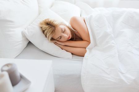 mujer en la cama: descanso, confort y la gente concepto - mujer durmiendo en la cama en el dormitorio en casa