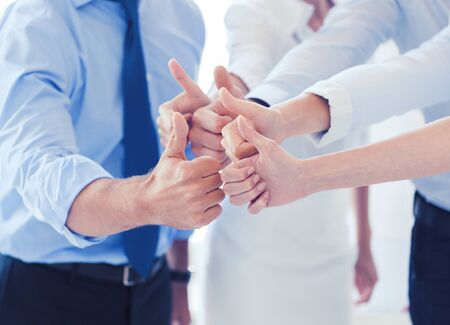team cooperation: success and winning concept - happy business team showing thumbs up in office Stock Photo
