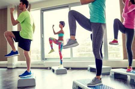 step fitness: fitness, sport, aerobics and people concept - group of smiling people working out and raising legs on step platforms in gym Stock Photo