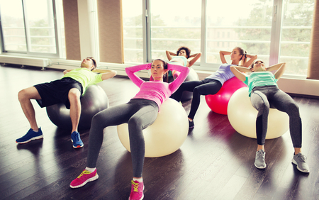 abdominal muscles: fitness, sport, training and lifestyle concept - group of people flexing abdominal muscles on fitball in gym