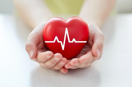 Gesundheit, Medizin, Menschen und Kardiologie Konzept - Nahaufnahme von Hand mit Kardiogramm auf kleinen roten Herzen