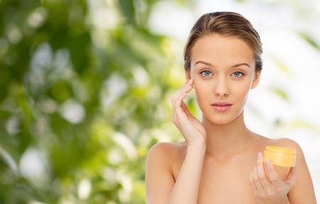 bellezza, la gente, cosmetici, cura della pelle e cosmetici concetto - giovane donna applicare la crema per il viso su sfondo verde naturale
