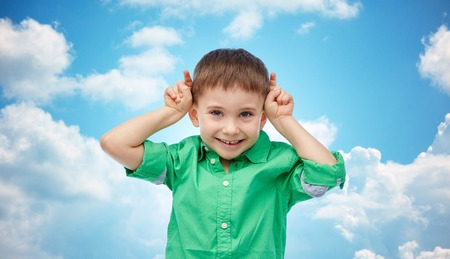 clouds making: childhood, fashion, fun and people concept - happy little boy having fun and making horns over blue sky and clouds background Stock Photo