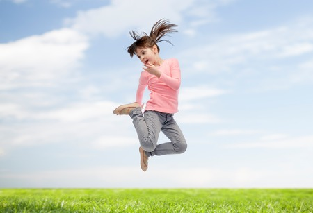 la felicidad, la infancia, la libertad, el movimiento y las personas concepto - niña feliz saltando en el aire sobre el cielo azul y el fondo de la hierba