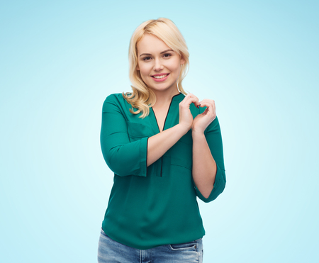 heart in hand: love, valentines day, gesture, plus size and people concept - smiling young woman in shirt and jeans showing heart shape hand sign over blue background