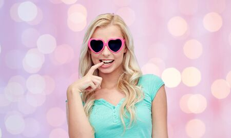and guessing: emotions, expressions, summer and people concept - smiling young woman or teenage girl in heart shape sunglasses over pink holidays lights background