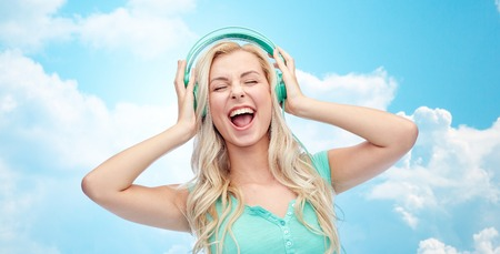 music, technology and people concept - happy young woman or teenage girl with headphones singing song over blue sky and clouds background