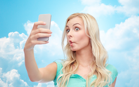 clouds making: expressions, technology and people concept - funny young woman or teenage girl taking selfie with smartphone and making fish face over blue sky and clouds background