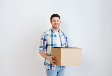 nice accommodations: moving, delivery, housing, accommodation and people concept - smiling young man with cardboard box at home Stock Photo