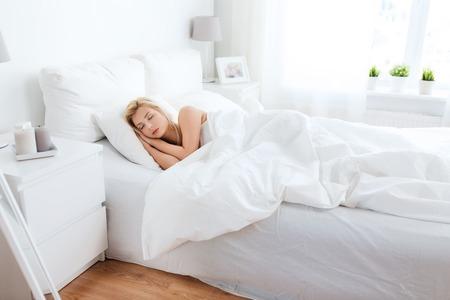 Concetto di resto, di comodità e della gente - giovane donna che dorme a letto a casa camera da letto Archivio Fotografico - 60072169