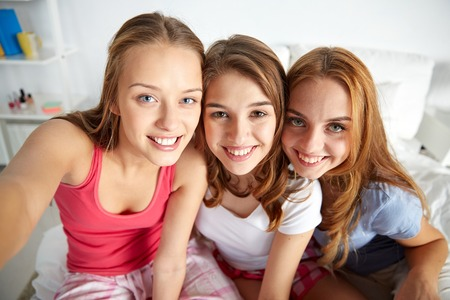 friendship, people, pajama party and fun concept - happy friends or teenage girls taking selfie at home