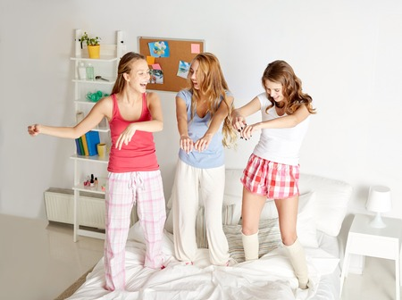 in pajama: friendship, people and pajama party concept - happy friends or teenage girls having fun, dancing and jumping on bed at home