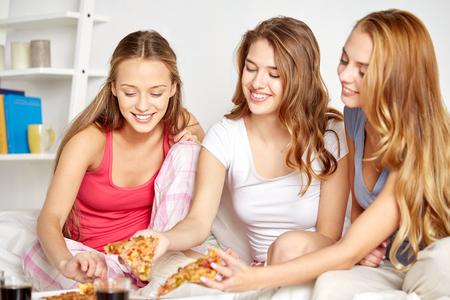 niña comiendo: amistad, gente, fiesta pijama y el concepto de la comida basura - amigos felices o adolescentes comiendo pizza en casa
