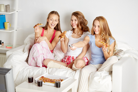pj's: friendship, people, pajama party, entertainment and junk food concept - happy friends or teenage girls eating pizza and watching movie or tv series at home