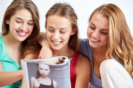 pajama party: friendship, people and pajama party concept - happy friends or teenage girls reading magazine at home Stock Photo