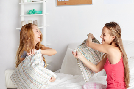 pj's: friendship, people and pajama party concept - happy friends or teenage girls having fun and pillow fight on bed at home