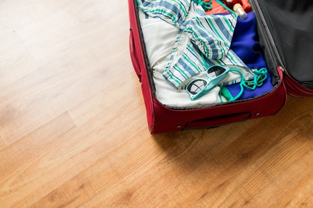beach clothes: summer vacation, travel, tourism and objects concept - close up of travel bag with beach clothes, sunglasses and sunscreen Stock Photo
