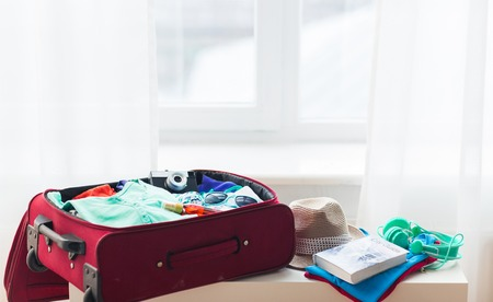 travel bag: summer vacation, travel, tourism and objects concept - close up of travel bag with clothes and stuff