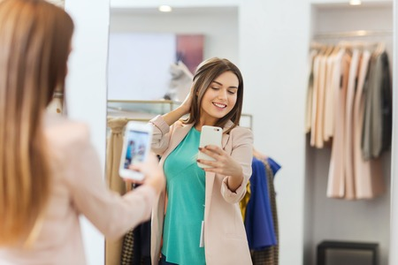 mirror: shopping, fashion, style, technology and people concept - happy woman with smartphone taking mirror selfie at clothing store